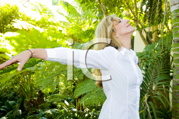 Royalty Free Photo of a Woman in a Garden With Her Arms Outstretched