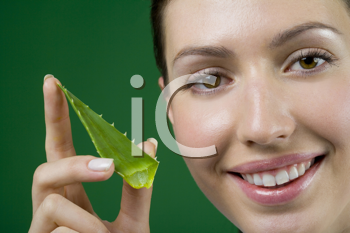 Royalty Free Photo of a Woman Holding an Aloe Leaf