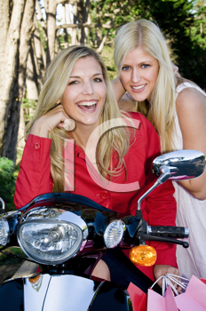 Royalty Free Photo of Two Women Leaning on a Scooter