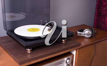 Vintage Stereo Turntable Plays White Vinyl Record Album, angled view