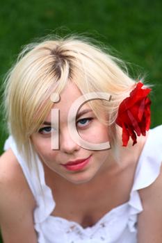 A stunningly beautiful young blond woman with red flower in hair