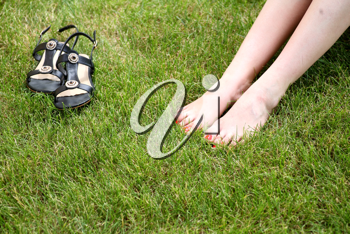 Womans bare feet on the fresh green grass and shoes