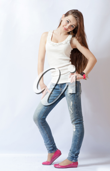Full length portrait of a caucasian blond woman in blue jeans and pink shoes on gray background