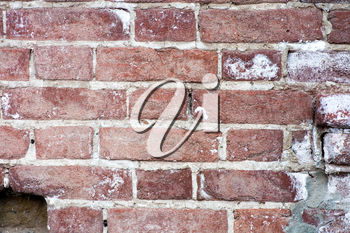 The old red brick wall. Red brick wall closeup background. It depicts an old brick wall crumbling