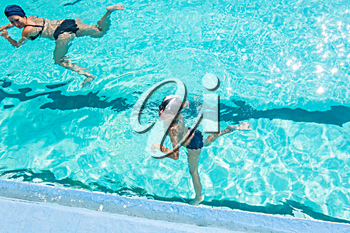Mother giving son a swimming lesson in pool during summer a lot of copyspace