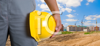 Royalty Free Photo of a Builder Holding a Yellow Hardhat