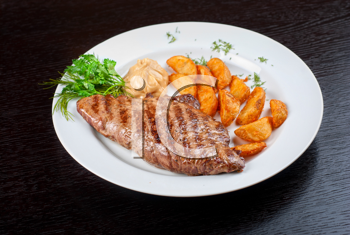 Juicy beef steak stuffed with beef tongue and cheese served with potatoes, greenery and sauce