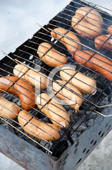grilled sausages on grill, with smoke above it