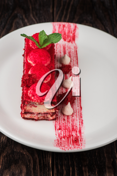 Plate with piece of delicious red velvet cake on dark wooden background