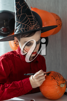 Halloween carnival or masquerade concept. Happy teen boy in costume drawing a pumpkin for the Halloween celebration.
