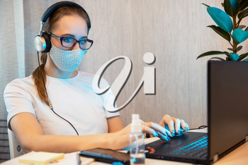 Woman in mask, working from home. Sanitizer anti virus spray on the working table. Coronavirus, quarantine for COVID-19 concept.