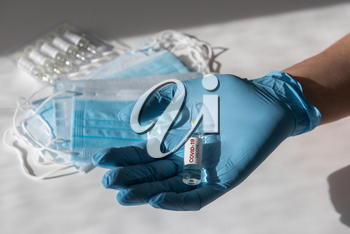 Coronavirus vaccine concept: covid-19 vaccine in doctor hand with blue protective gloves.