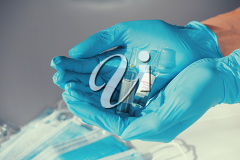 Coronavirus vaccine concept: covid-19 vaccine in hand with blue protective gloves.
