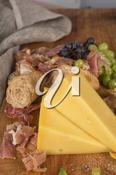 Fresh grapes, cheese bacon berries and salami on wooden table