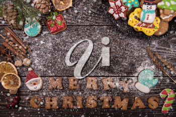Gingerbreads for new years and christmas on wooden background with space for design