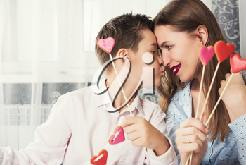 Happy Valentine's Day or Mother's Day. Young boy spends time with his mum and celebrates with gingerbread heart cookies on a stick.