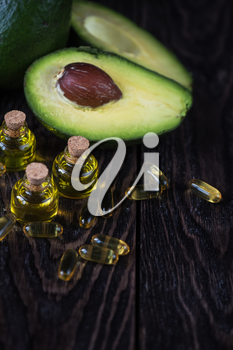 Oil of avocado with fish oil pills on a dark wooden background