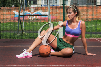 A young beauty athletic woman in sportswear with basketball ball