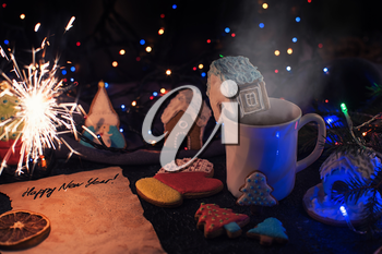 Christmas cookies and cup of tea on daark color bokeh lights background