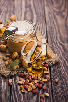 Natural peanut butter with oil in a glass jar and peanuts