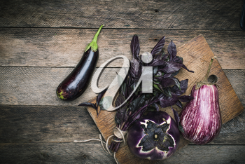 Aubergines and basil on chopping board and wooden table. Rustic style and autumn food photo
