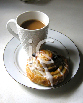 Royalty Free Photo of a Cup of Coffee and a Cinnamon Bun