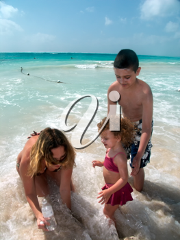 Happy family playing in the surf on the caribbean beach.