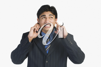 Businessman with his fingers in ears