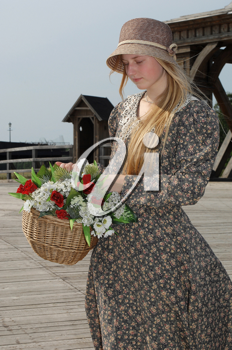 Royalty Free Photo of a Girl in a Hat With a Basket of Flowers