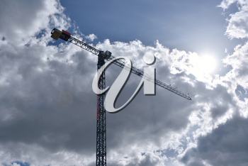 Construction crane against the sky with clouds.