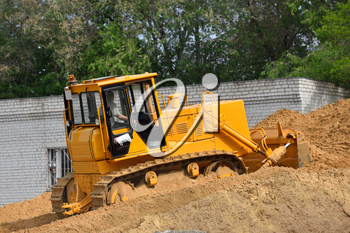 A bulldozer rakes the sand uphill in the warehouse.