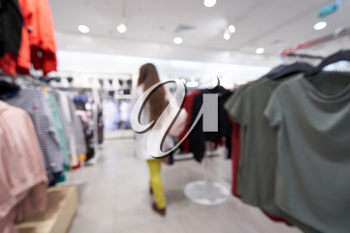 Beautiful blurred background of a women's clothing store in a mall, a girl walks and chooses clothes. Defocused