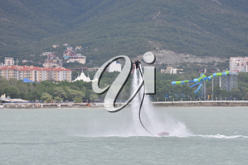 Beautiful show on the water, sports team fly on flyboards in the sea against the background of the mountains