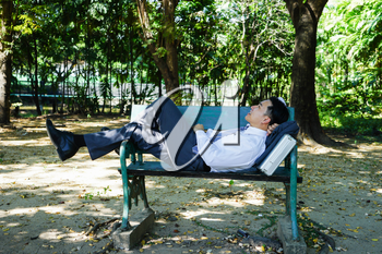 Asian businessman is lying on bench.