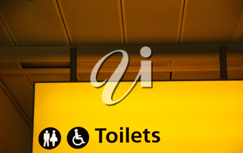 Royalty Free Photo of a Yellow Public Toilet Sign