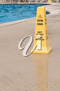 Royalty Free Photo of a Yellow Caution Sign Next to a Swimming Pool