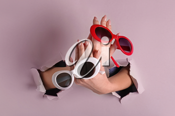 Female hands with stylish sunglasses on color background