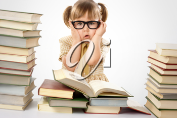 Royalty Free Photo of a Little Girl in Black Glasses Surrounded by Books