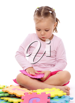Royalty Free Photo of a Little Girl Playing With Foam Puzzle Pieces