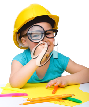Royalty Free Photo of a Little Girl Wearing Glasses and a Hardhat Holding a Magnifying Glass