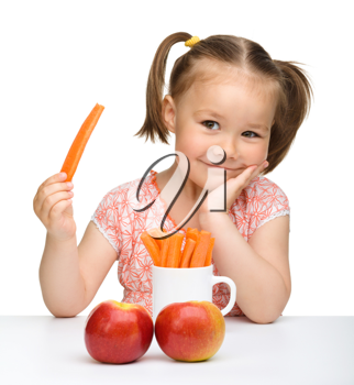 Royalty Free Photo of a Little Girl With Apples and Carrot Sticks