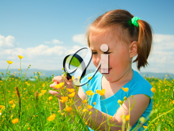 Royalty Free Photo of a Little Girl Looking at Flowers With a Magnifying Glass