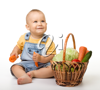 Royalty Free Photo of a Baby on the Floor With a Basket of Vegetables