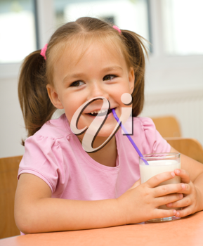 Royalty Free Photo of a Little Girl Drinking Milk Through a Straw