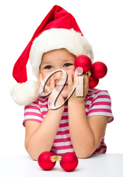 Royalty Free Photo of a Little Girl Wearing a Santa Hat and Holding Ornaments