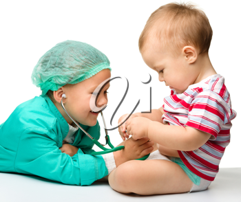 Royalty Free Photo of a Girl Playing Doctor With Her Baby Brother