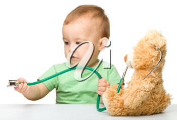 Royalty Free Photo of a Baby With a Teddy Bear and a Stethoscope