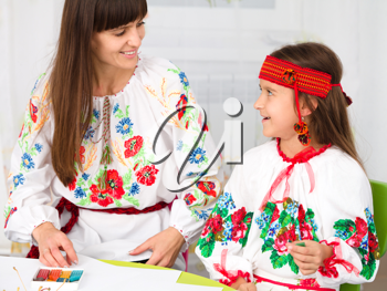 Royalty Free Photo of a Ukrainian Mother and Child in Traditional Dress Doing Crafts