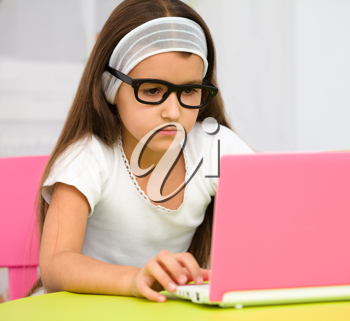 Royalty Free Photo of a Little Girl Wearing Glasses Sitting at a Pink Laptop