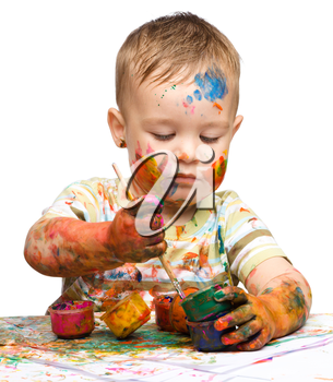 Portrait of a cute little boy messily playing with paints, isolated over white